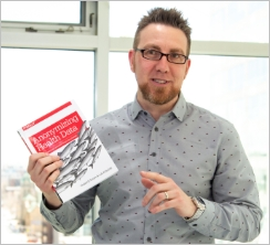 Chief Methodologist Luk Arbuckle Holding Book